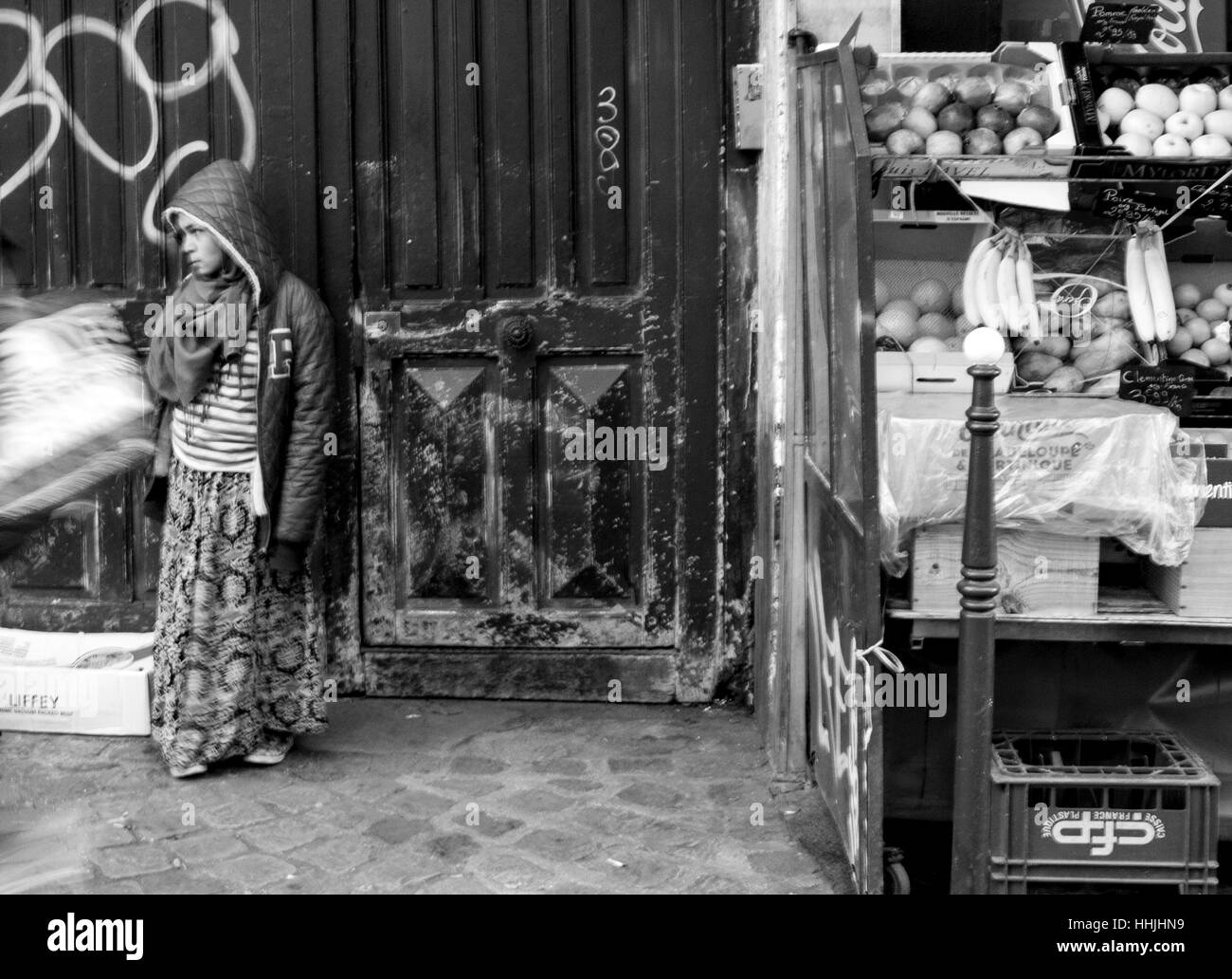 Gypsy girl outside the door of her home in Paris. - Stock Image