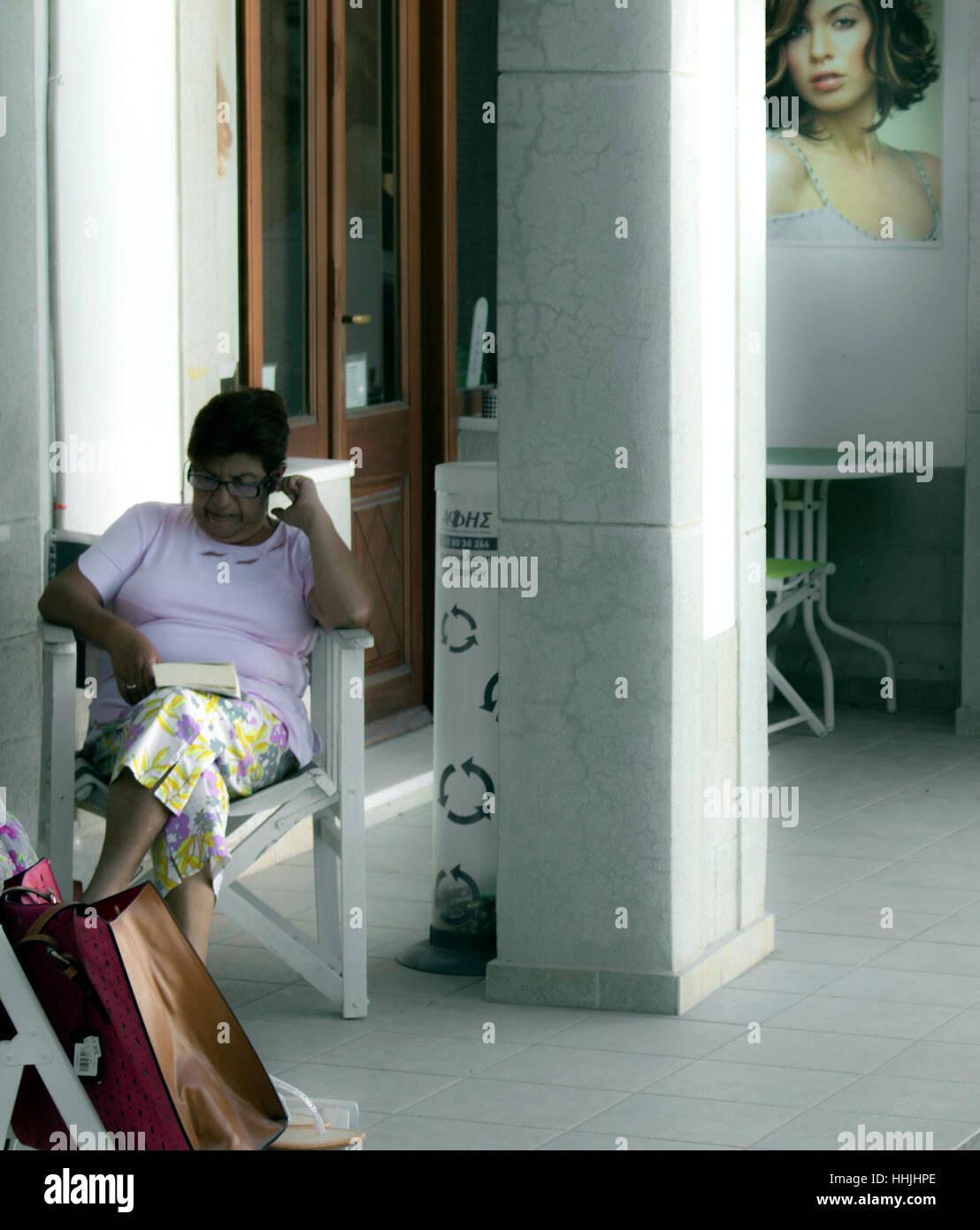 Woman Reading A Magazine Outside Beauty Salon