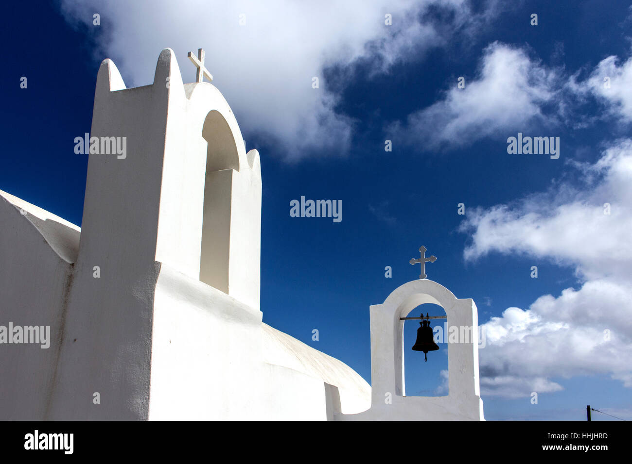 Two tower bells and cross view from below in Santorini. - Stock Image