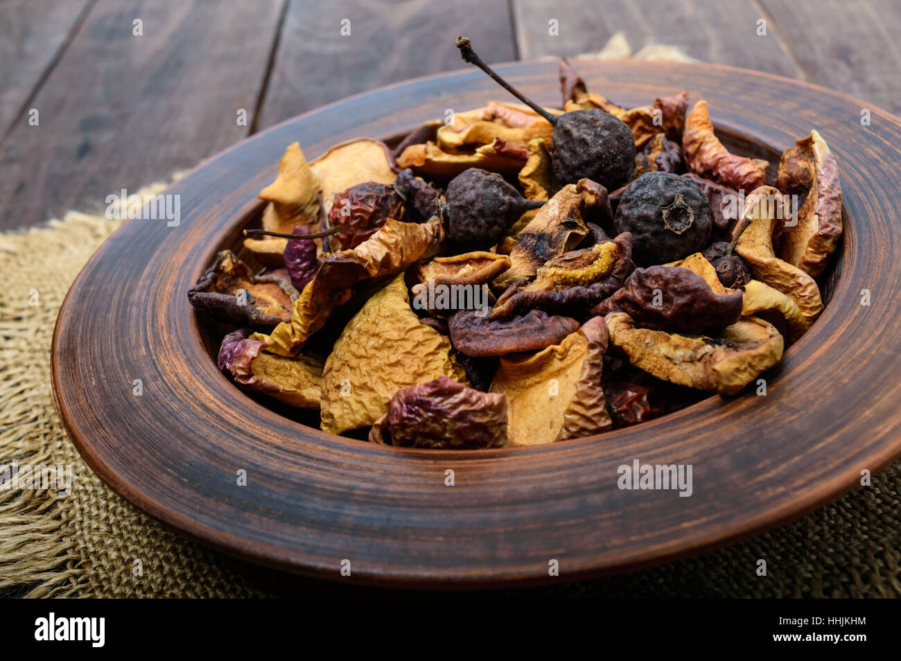 Dried fruit (apples, pears, apricots), berries in a bowl on dark wooden background. Close up. Ingredients for the - Stock Image