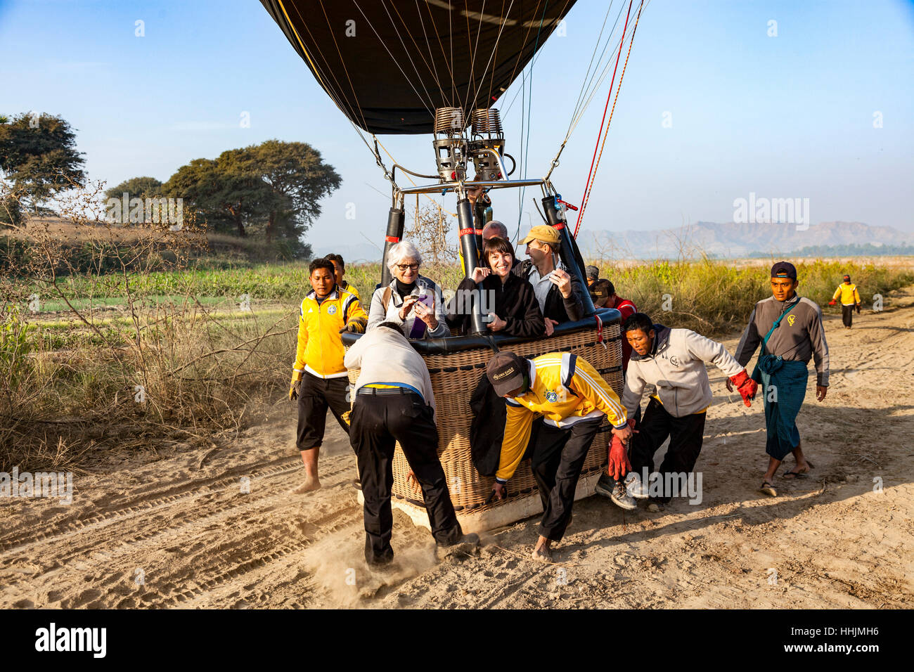 After landing, positioning of a balloon by the crew in a spot protected from the wind and prickly shrubs (Old Bagan - Myanmar). Stock Photo