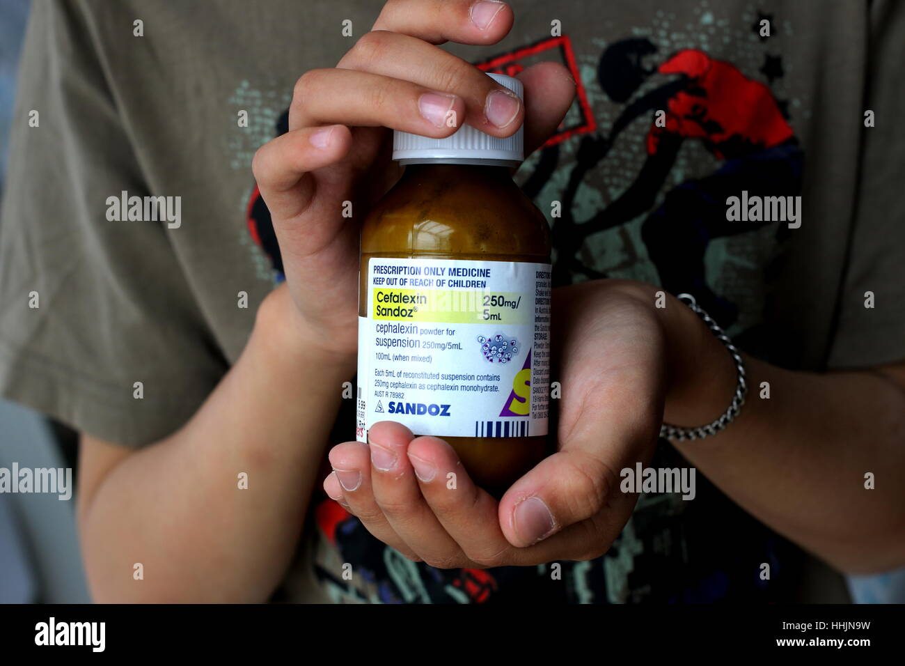 Hand Holding Cefalexin Sandoz antibiotic - Stock Image