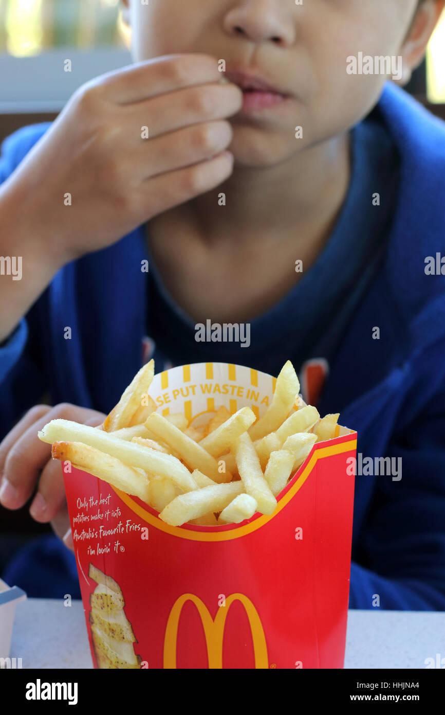 Close up of a child eating  McDonald's  potato chips in McDonald's Melbourne Victoria Australia - Stock Image