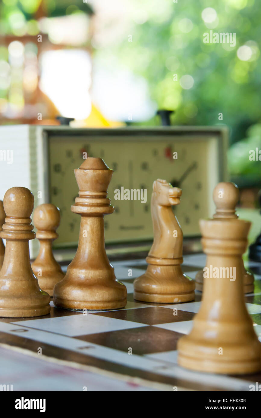 chessmen and hours on a board in clear summer day - Stock Image