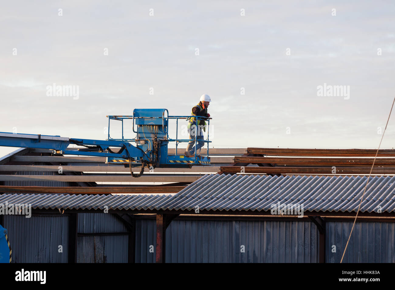 Construction worker with hardhat and reflective vest operates Stock