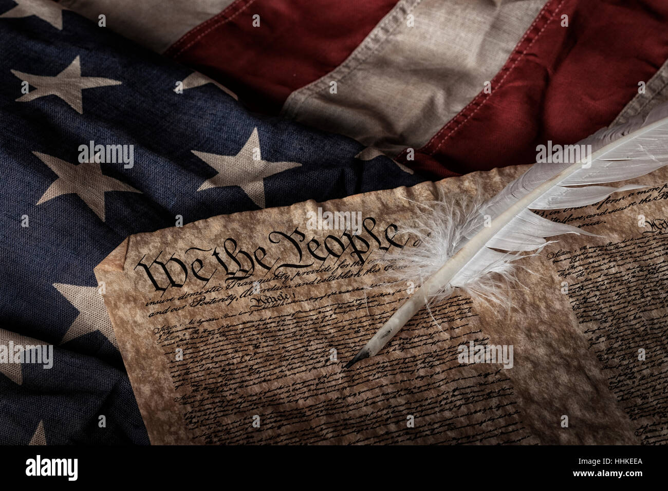 U.S. constitution and quill pen on an old and worn US flag - Stock Image