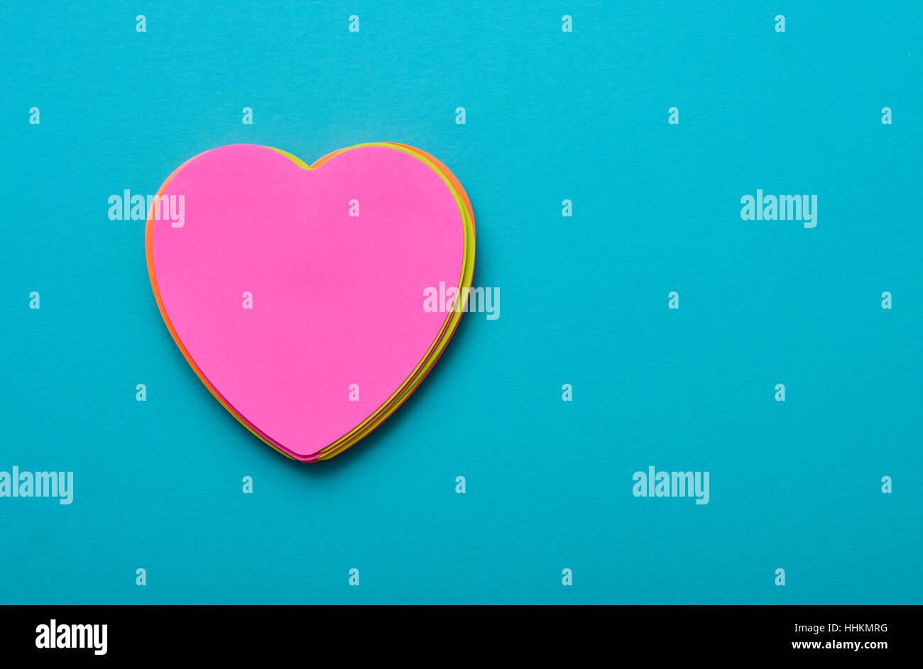a stack of heart-shaped sticky notes of different colors topped by a pink one with a blank space in it on a blue Stock Photo