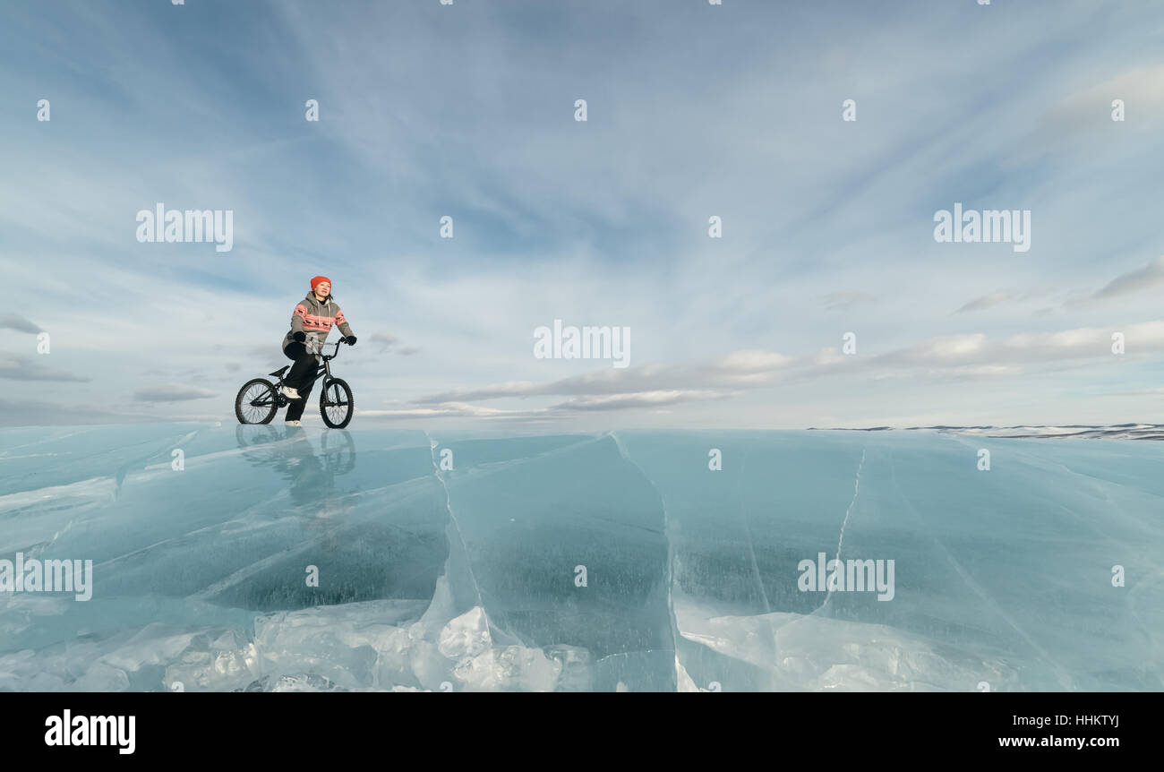 Girl standing on a bmx on the beautiful and dangerous ice. - Stock Image