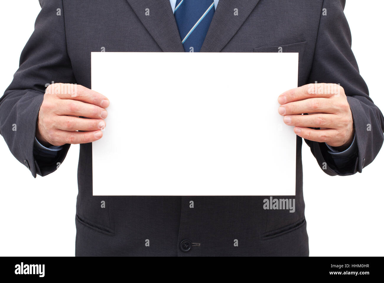 Businessman in suit holding a blank white sheet in his hands. - Stock Image