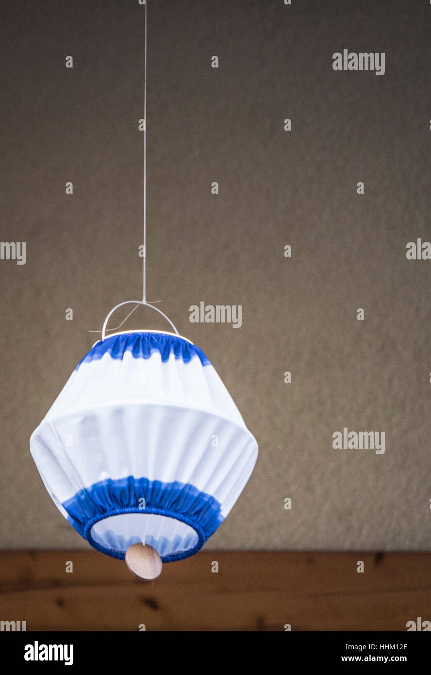 Hanging self made lamp in front of a wall - Stock Image