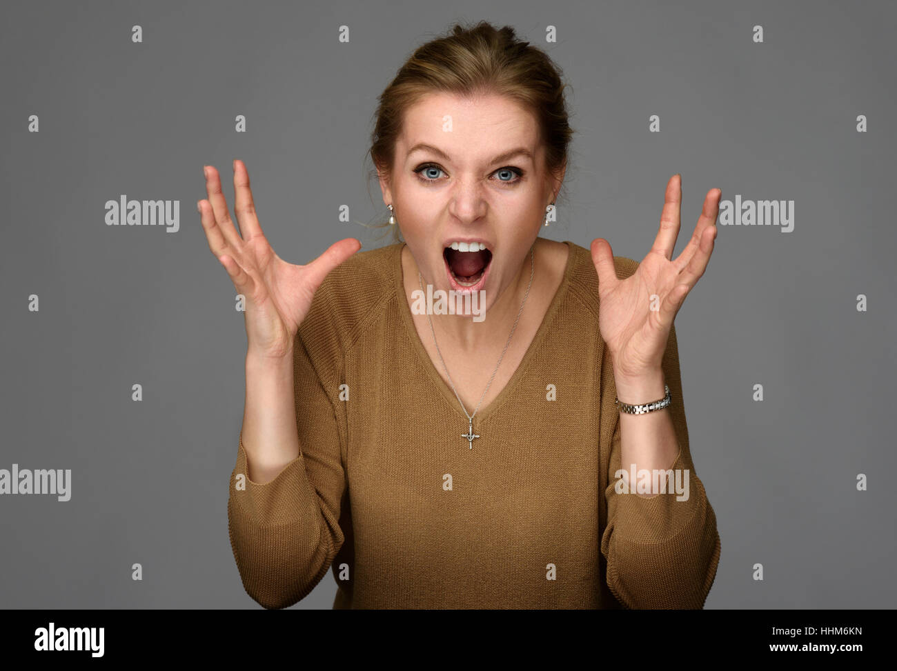 portrait of an angry woman over gray background - Stock Image