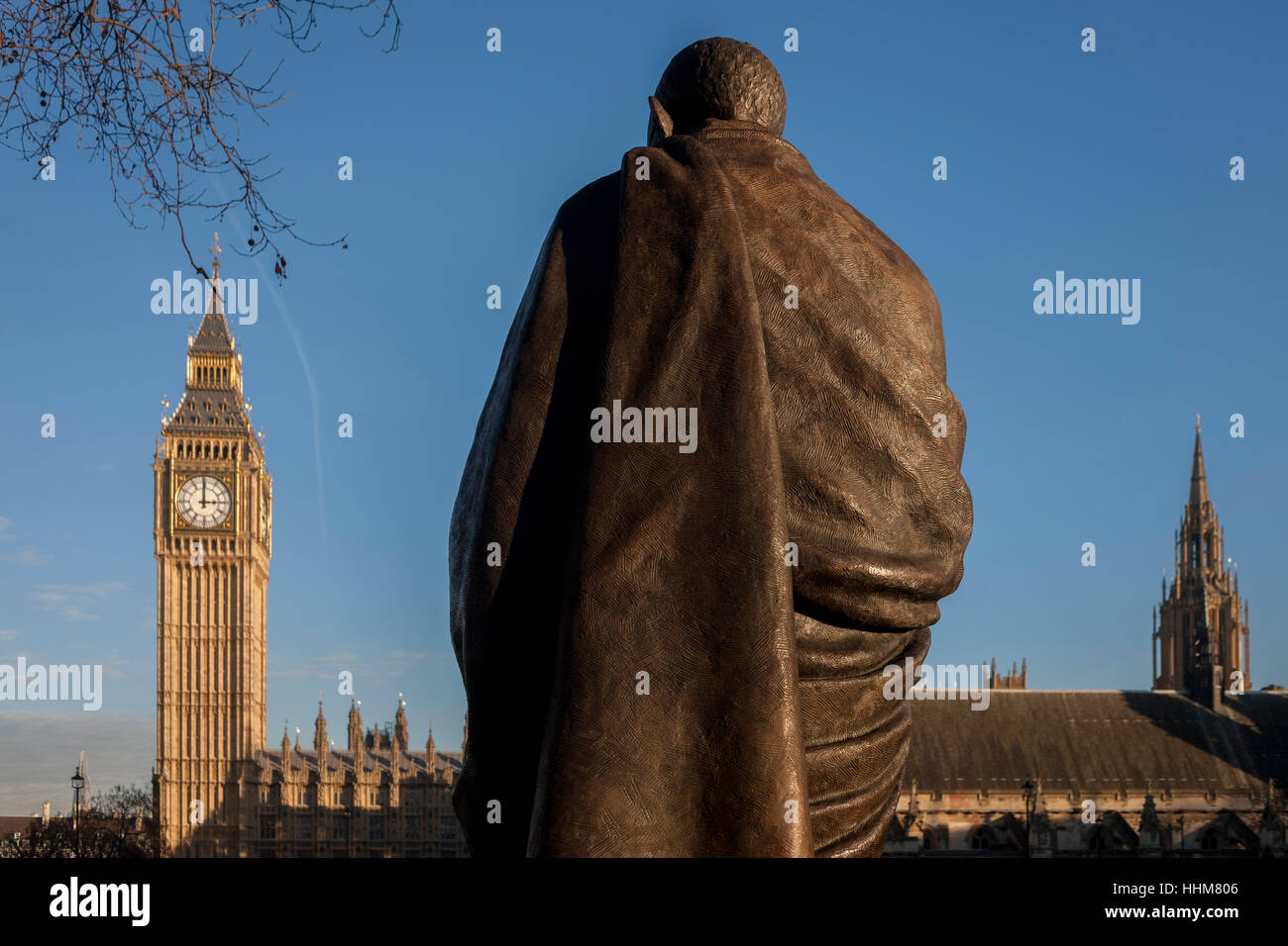 The monument to Indian leader Mahatma Gandhi with the British Houses of Parliament in the background, on 18th January - Stock Image
