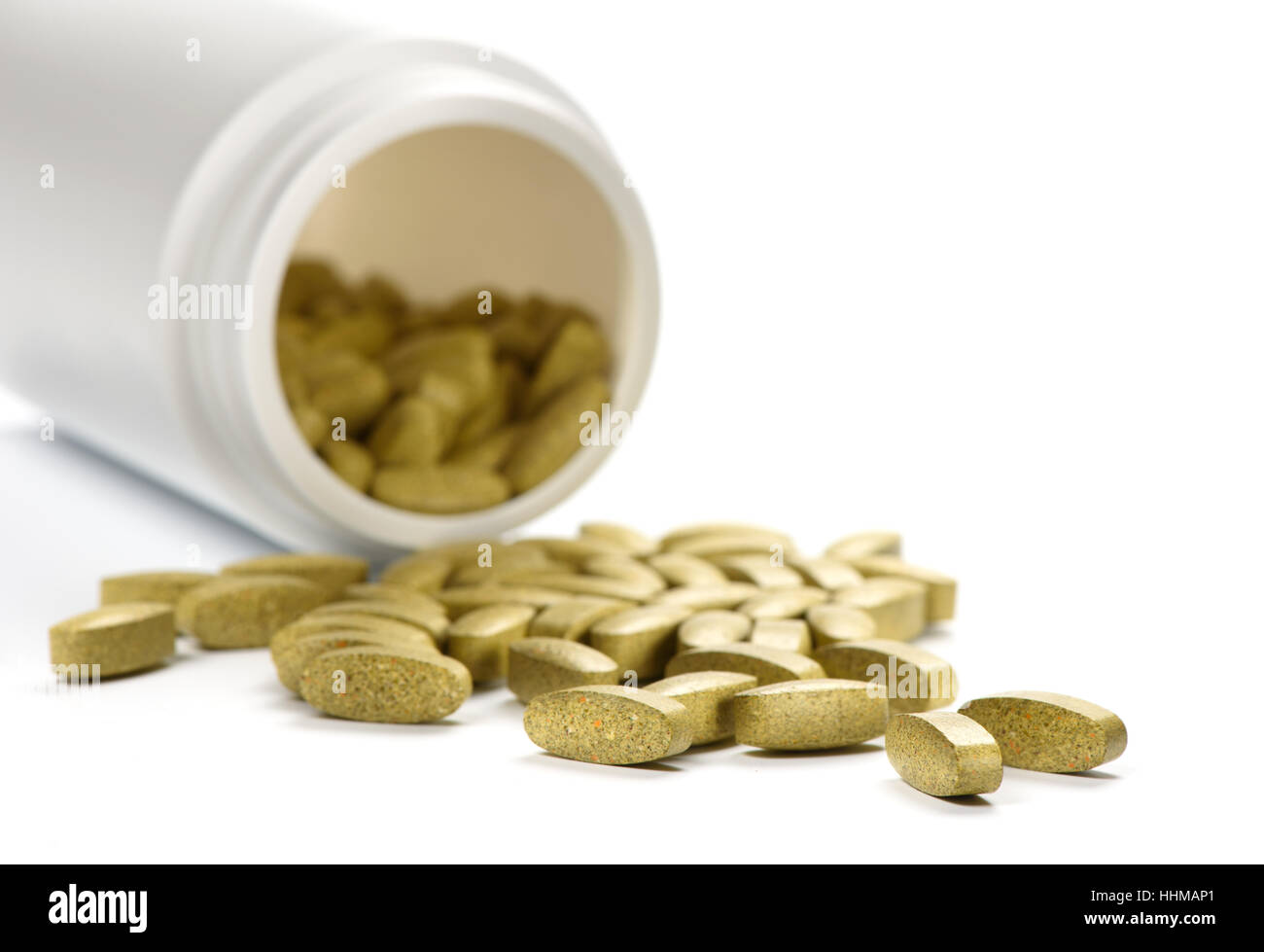 Green tablets with medical bottle. dietary supplements on a white background - Stock Image