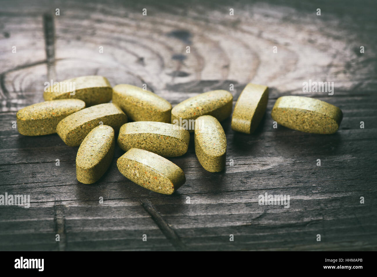 Green tablets. dietary supplements on a wooden table - Stock Image