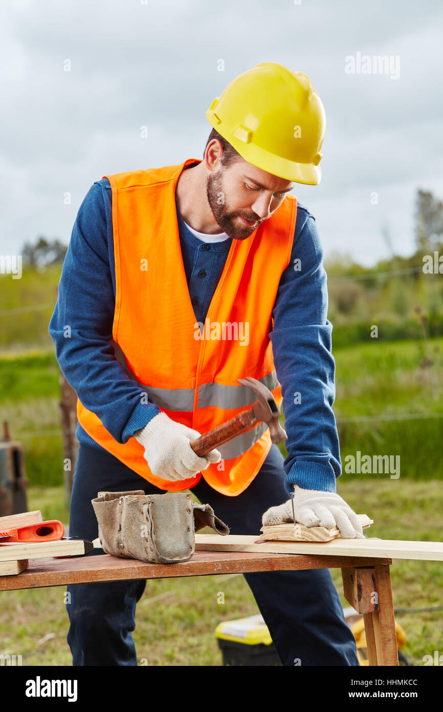 Carpenter hammering and working with wood at construction site - Stock Image