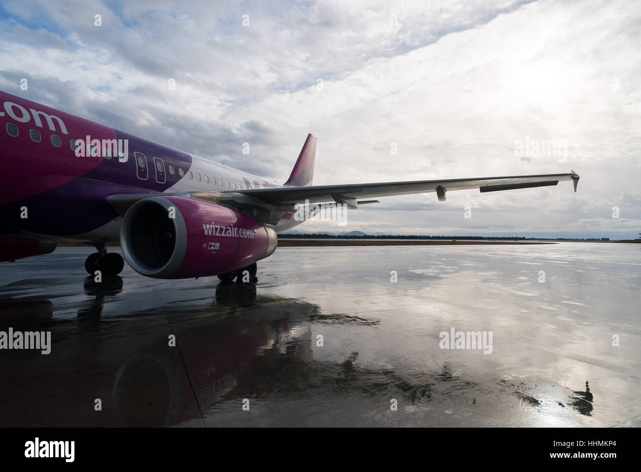 a Wizz Air Airbus A320 is ready for boarding on a cold wet day in Podgorica, Montenegro - Stock Image