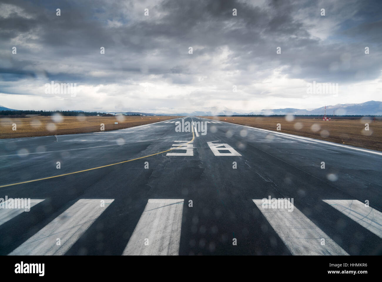 Water droplets speckle the lens at the threshold of a runway on a cold rainy day - Stock Image