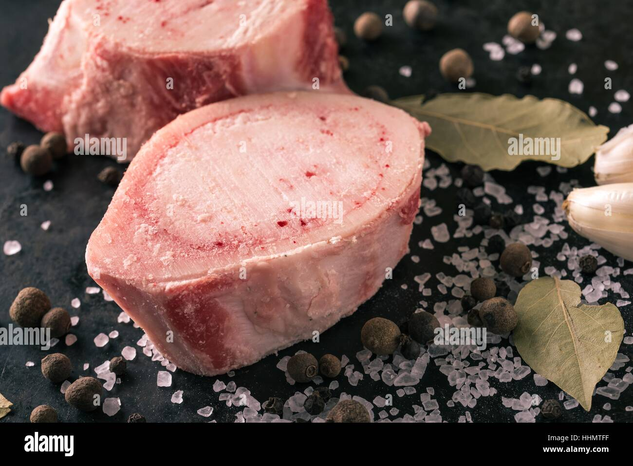 Horizontal photo with two pieces or slices of big marrowbone with few drops of blood and meat on side. Bones are - Stock Image
