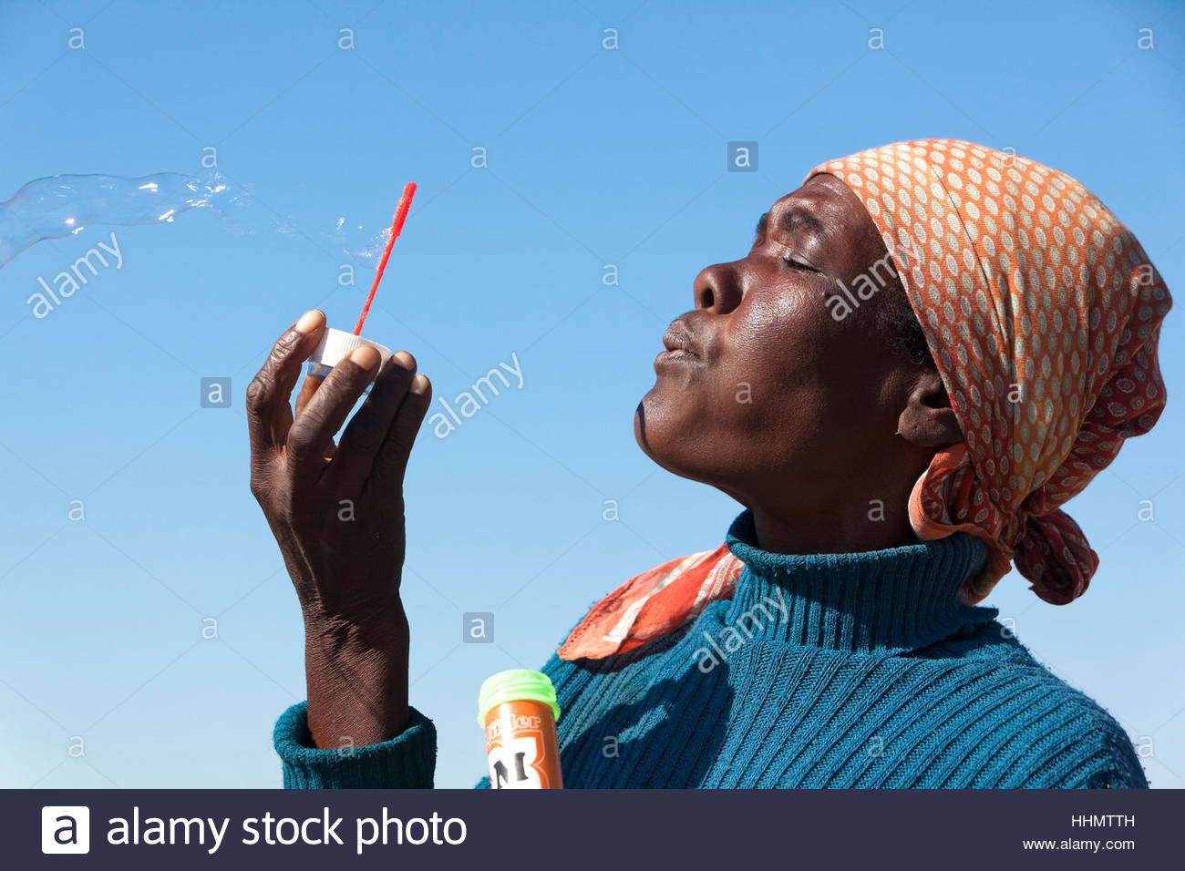 African woman blowing bubbles, Botswana - Stock Image