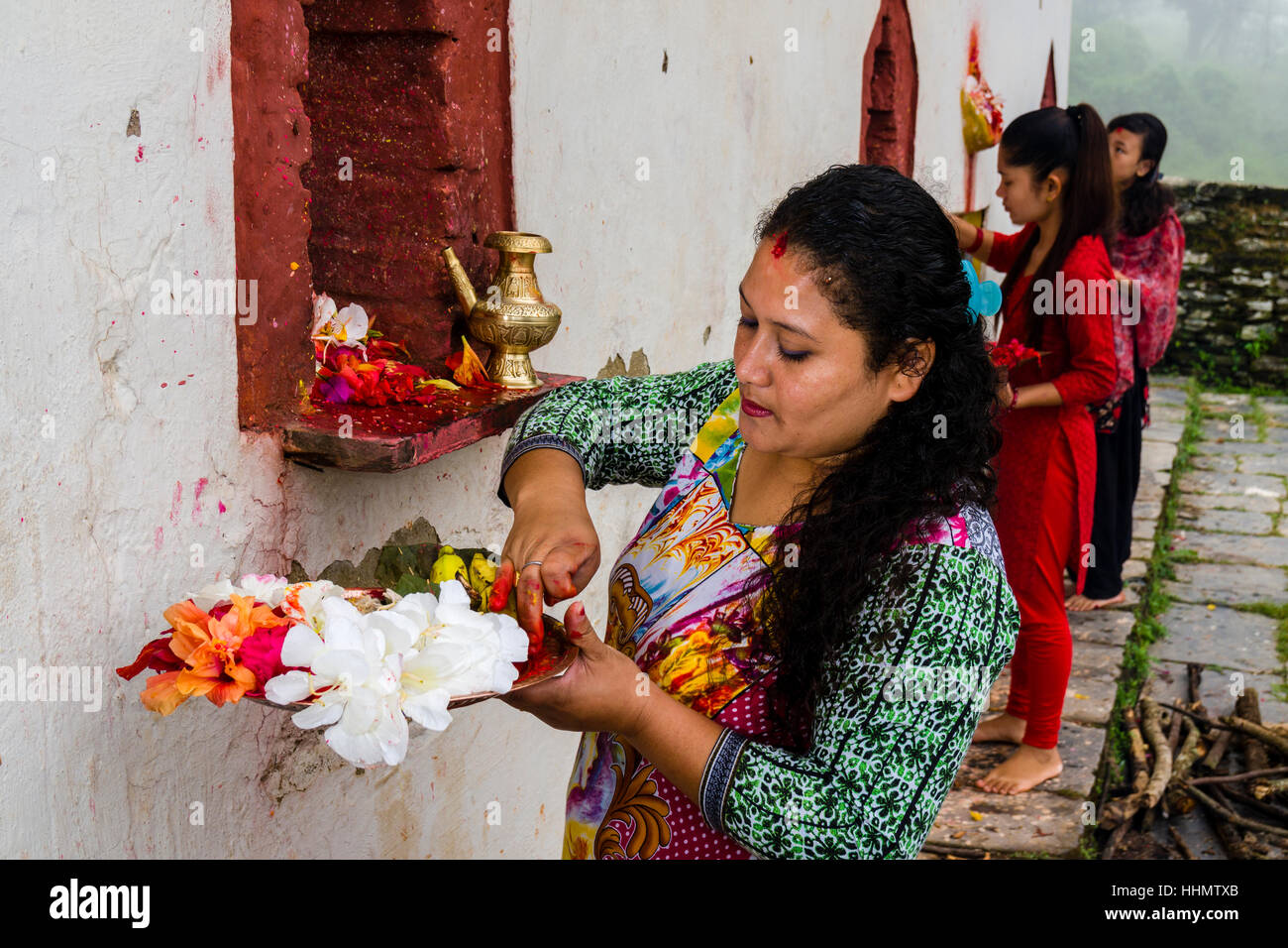 Woman is offering prasad to the statues of gods at hinduist festival Darsain, temple Khadga Devi Mandir - Stock Image