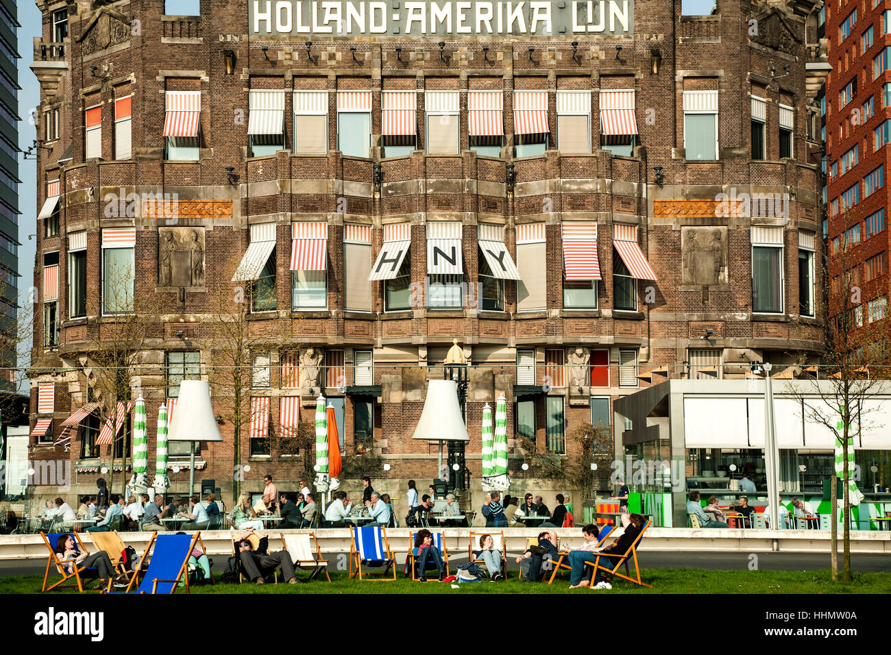People lounging in front of Hotel New York (formerly Holland-Amerika Lijn building), Rotterdam, Netherlands - Stock Image