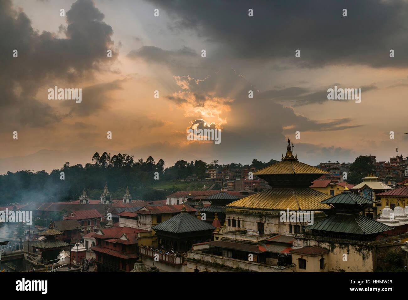 Sunset over the buildings of Pashupatinath temple, the banks of Bagmati River, Kathmandu, Kathmandu District, Nepal - Stock Image