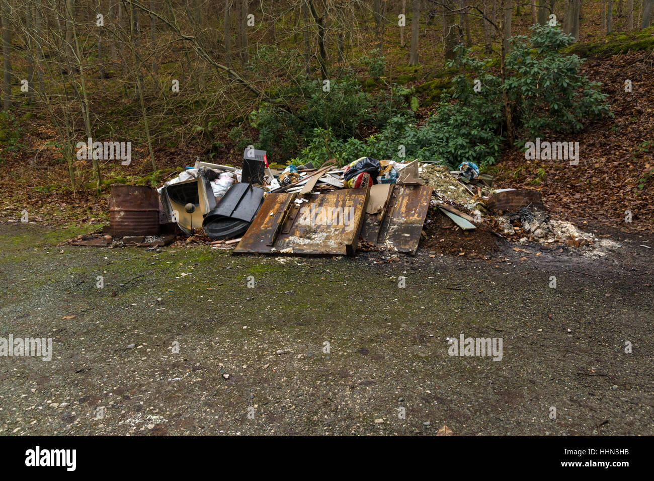 Dumped rubbish and garbage in a forest an example of fly tipping or illegal dumping on a forest trail in North Wales - Stock Image
