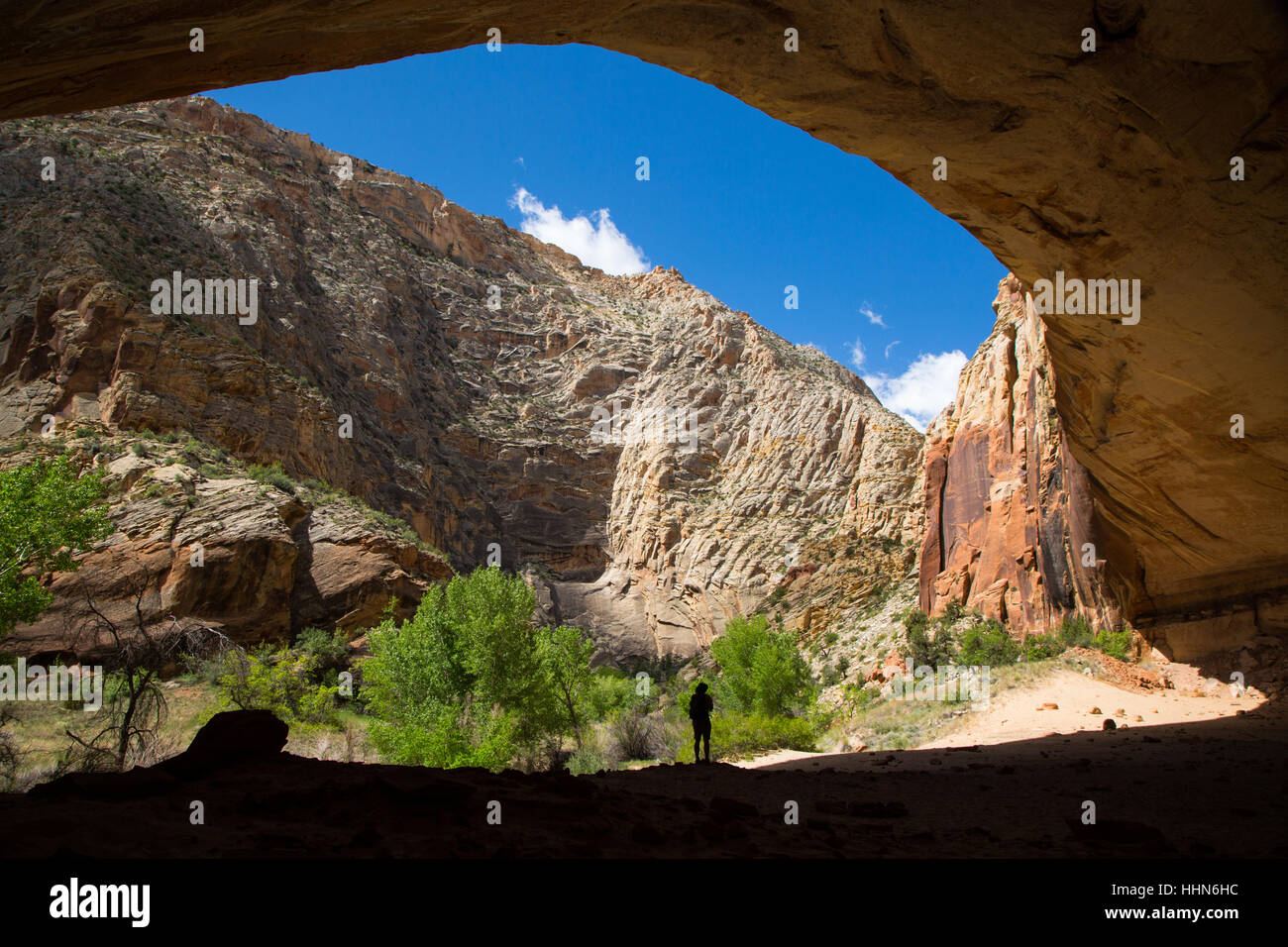 A male hiker standing at the base of a large sandstone alcove. Grand Staircase-Escalante National Monument, Utah Stock Photo