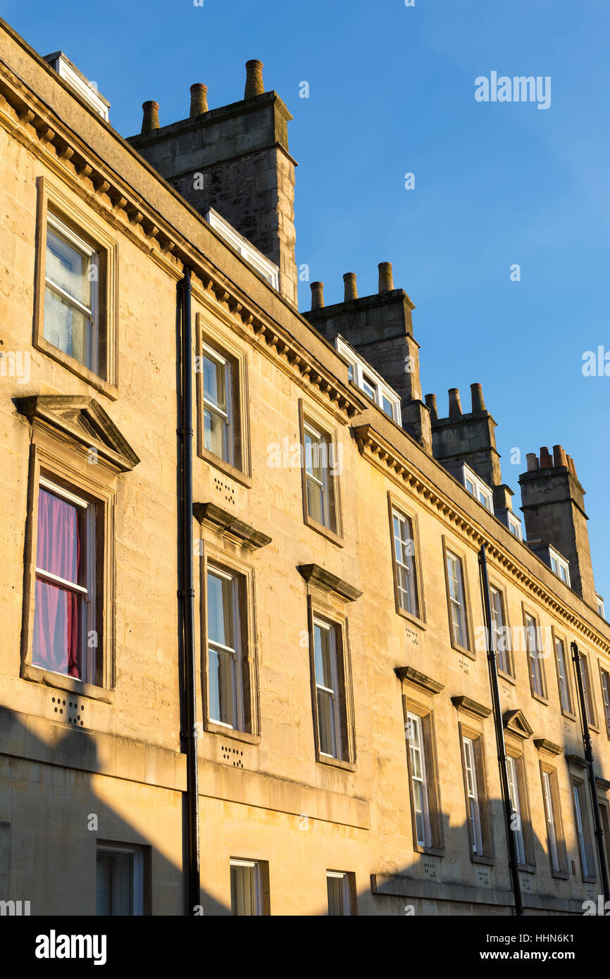 Top section of a row of stone houses in a terrace in Bath, UK. - Stock Image