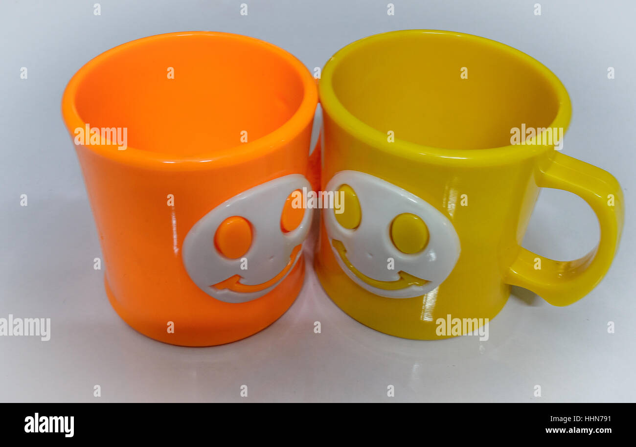 Colourful cups on a glossy white table. - Stock Image