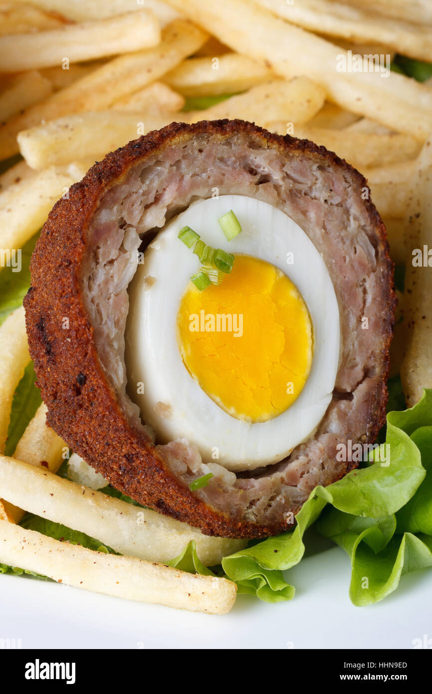 by scotch egg with french fries and lettuce on a plate macro. vertical - Stock Image