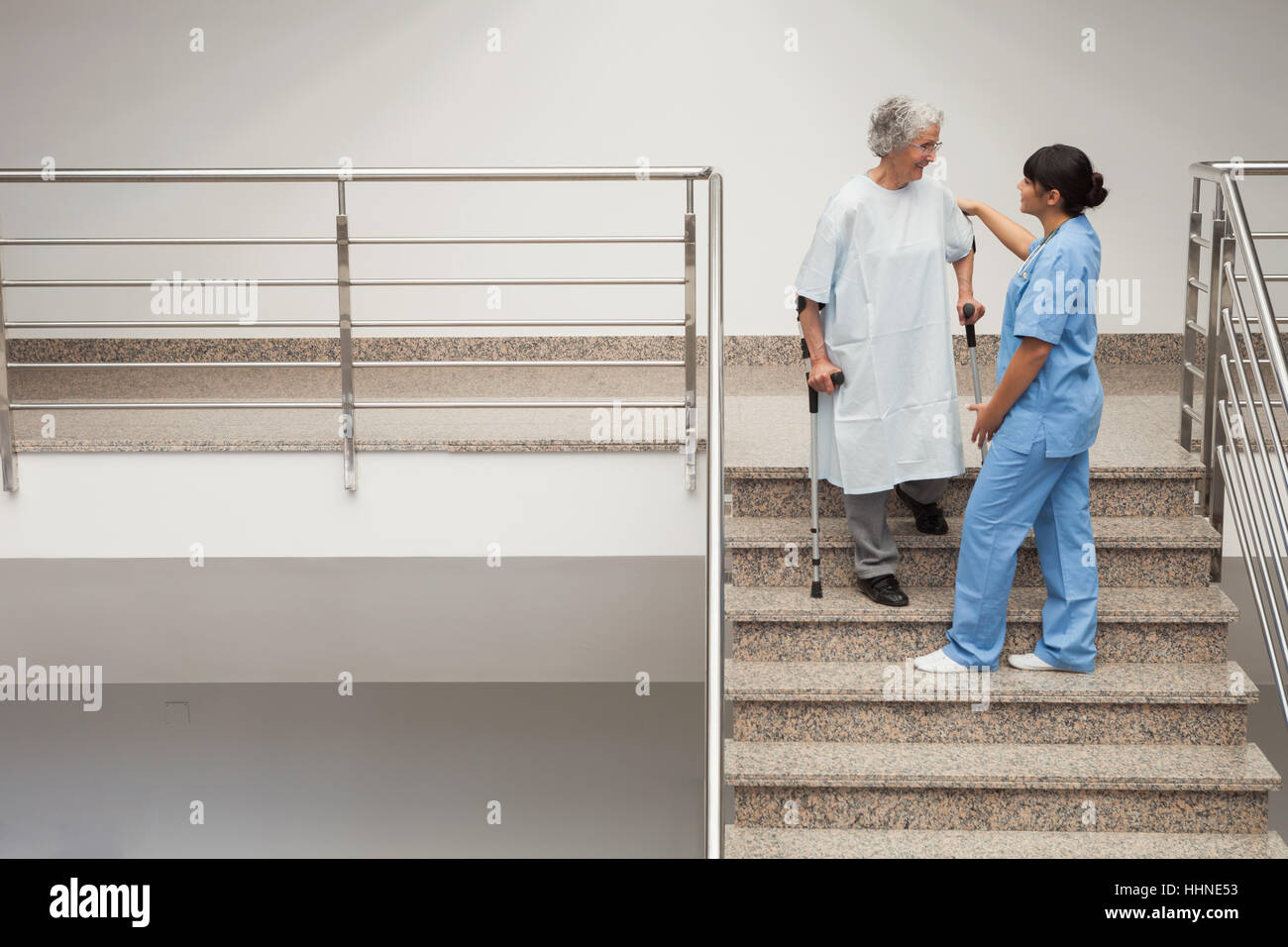 Nurse Helping Elderly Lady On Crutches Get Down Hospital Stairs