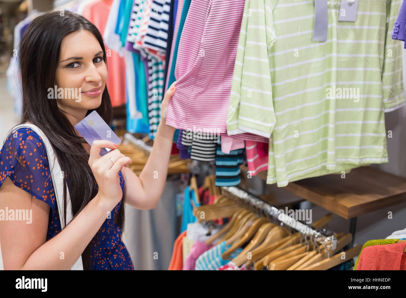 Woman Holding Credit Card Beside Clothing Display In Clothes Store