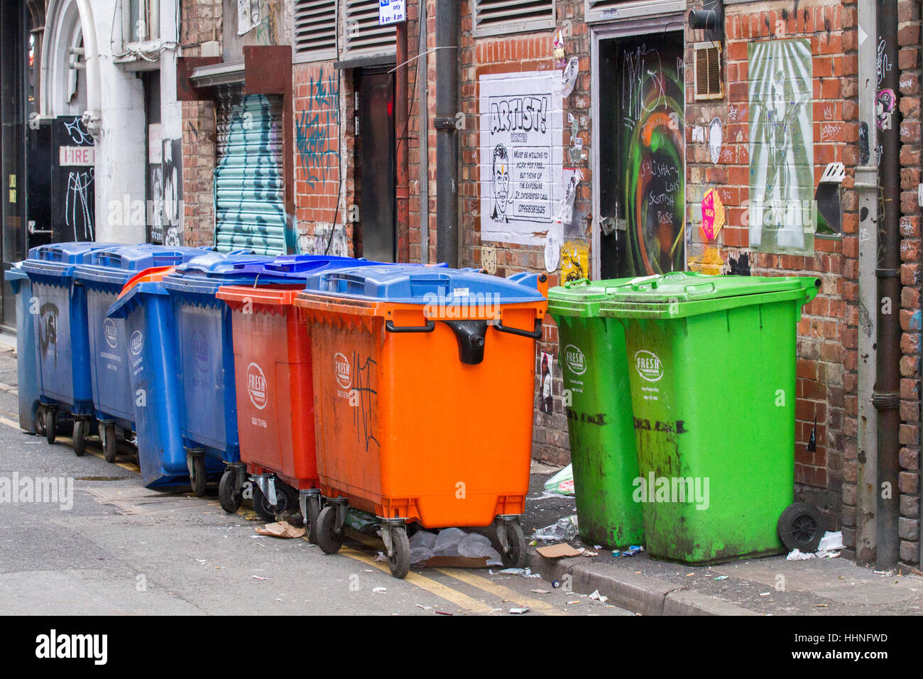 A line of multicoloured dumpsters behind stores in Manchester City centre - Stock Image