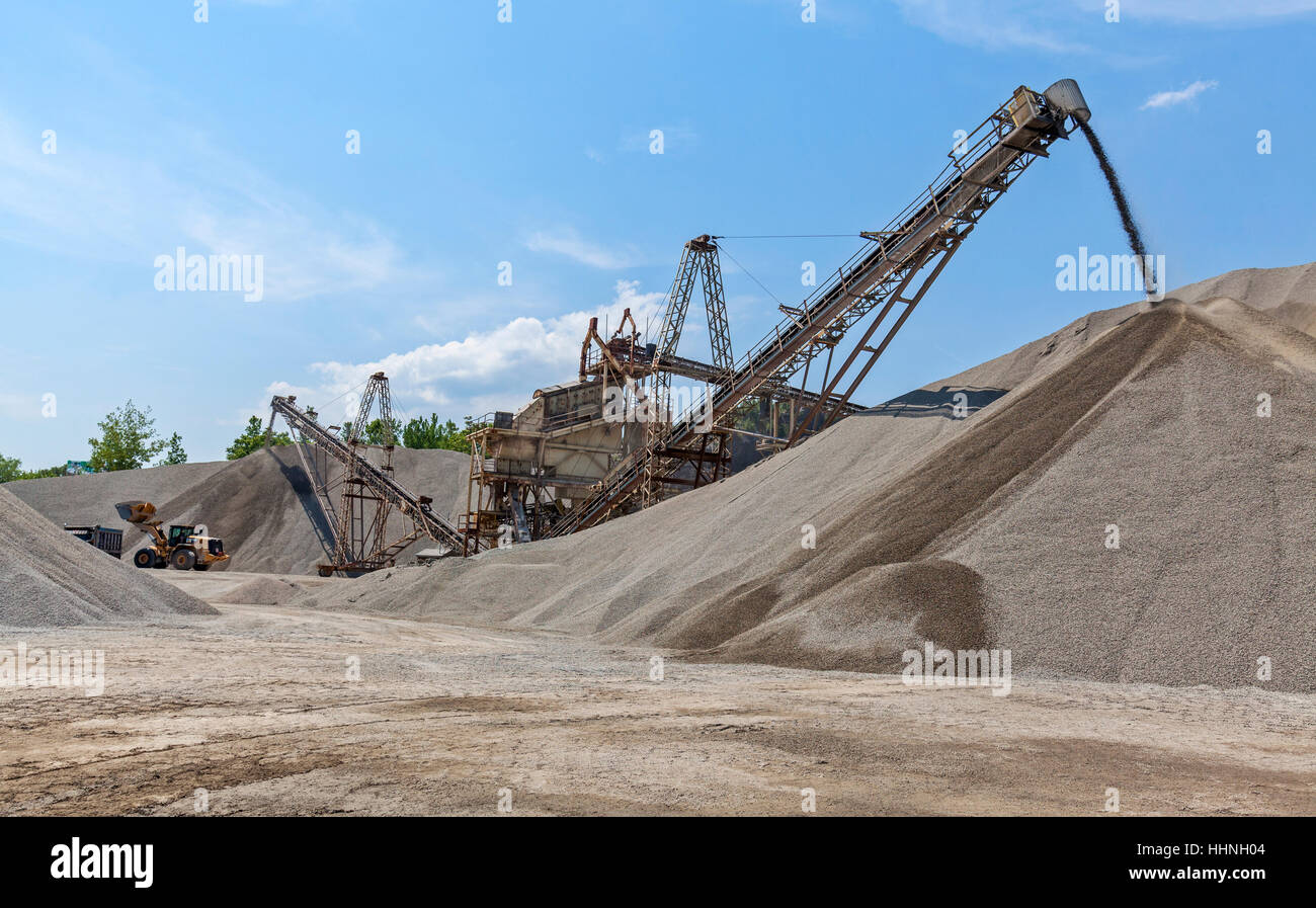 A conveyor belt transports crushed rock in a rock quarry into large mounds. - Stock Image