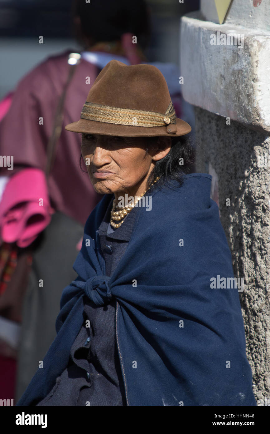 August 5, 2016 Otavalo, Ecuador: an elderly indigenous woman sitting in the sun outdoors dressed traditionally - Stock Image