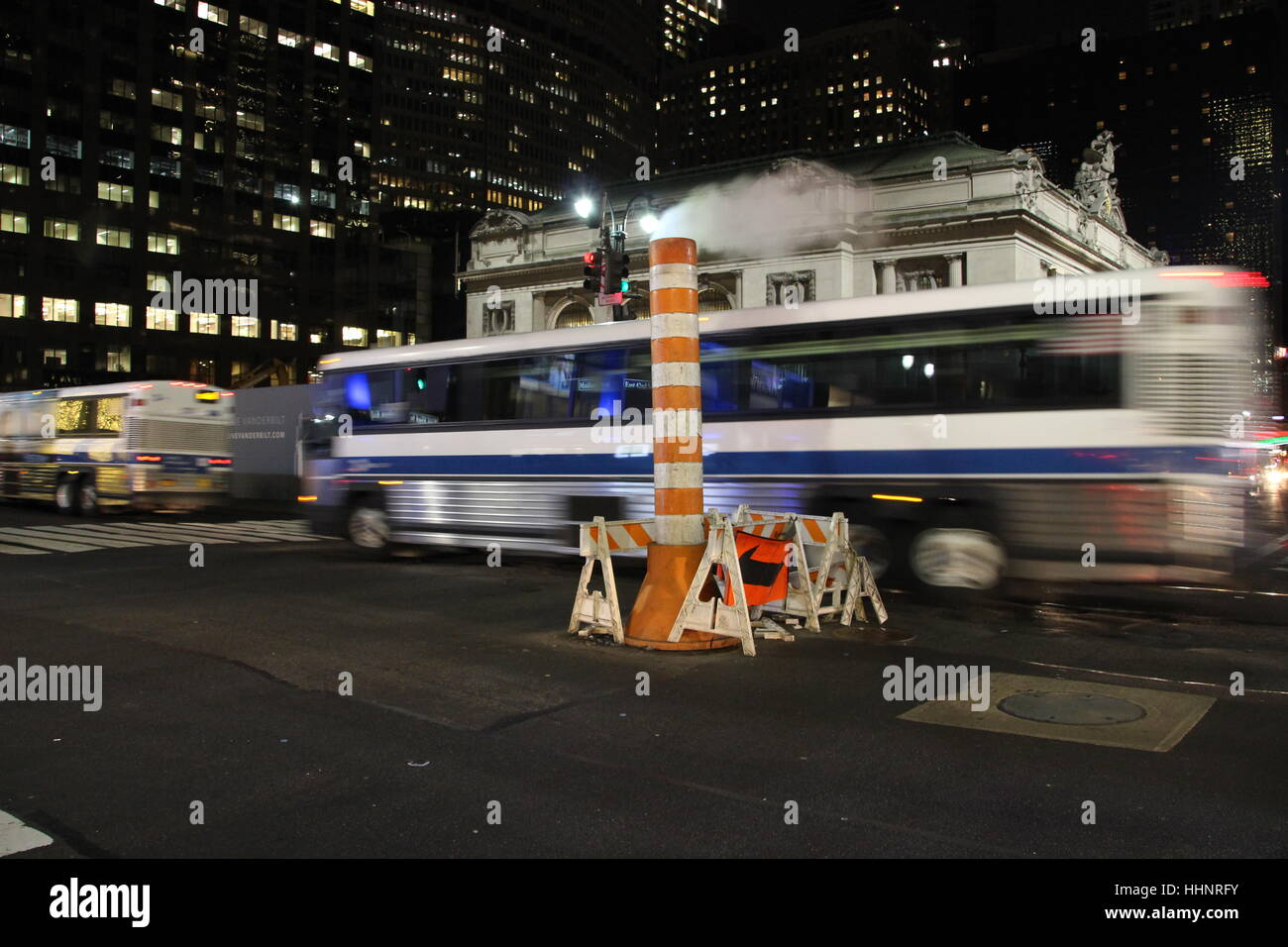 New York city steam vapor being vented through Consolidated Edison orange and white stack in middle of a junction - Stock Image