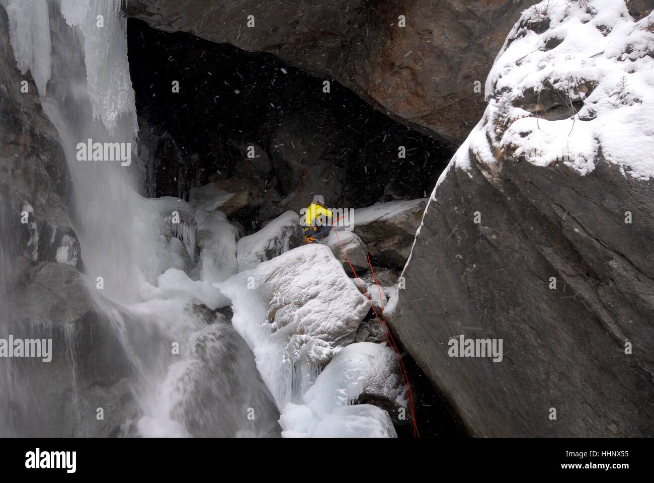 Photographer securing himself in place next to ice climbing route on partially frozen waterfall preparing to photograph Stock Photo