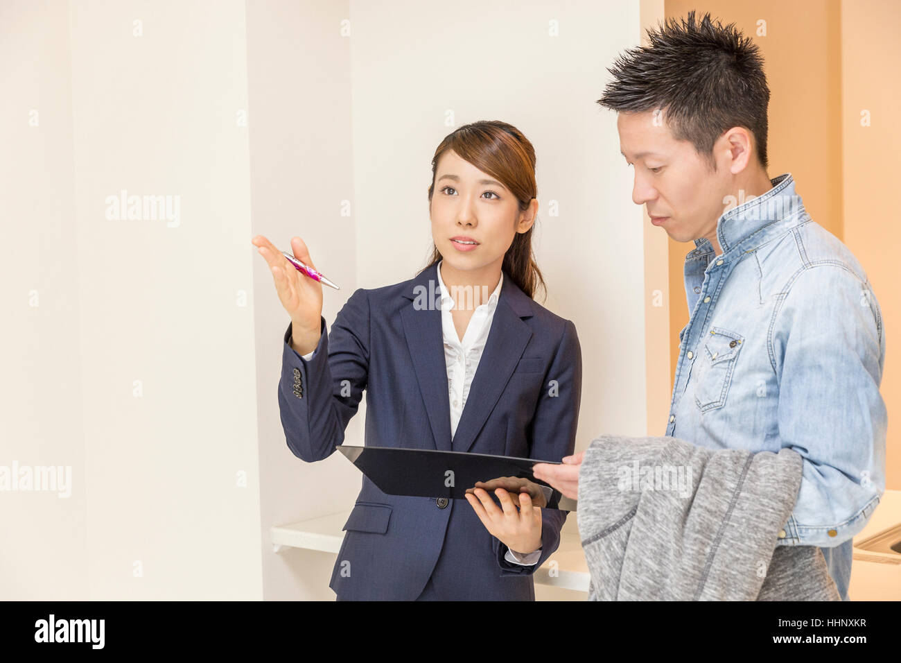 Real Estate Agent Showing Apartment to Buyers - Stock Image