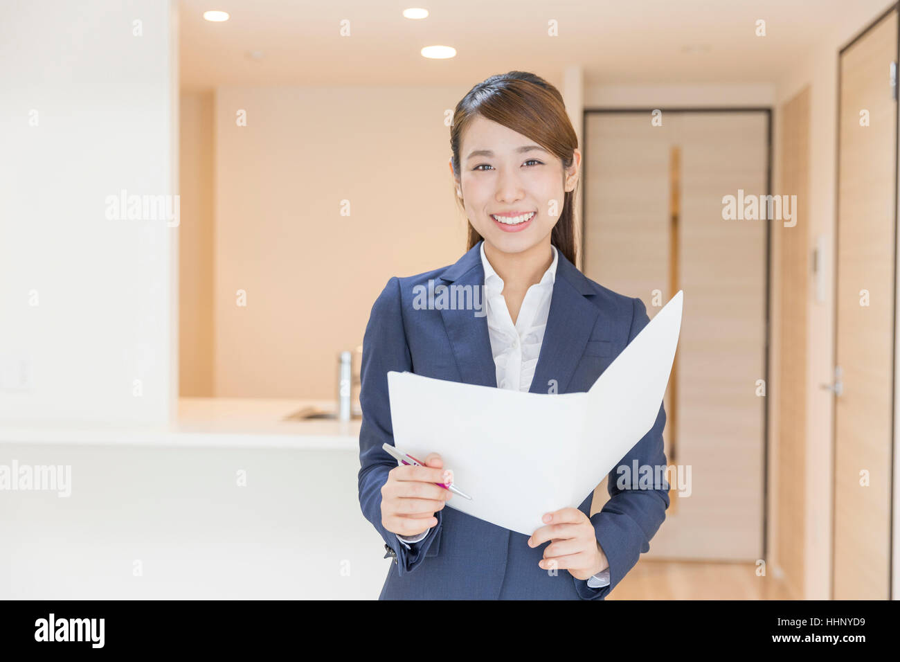 Woman Smiling to the Camera with Floor Plan - Stock Image