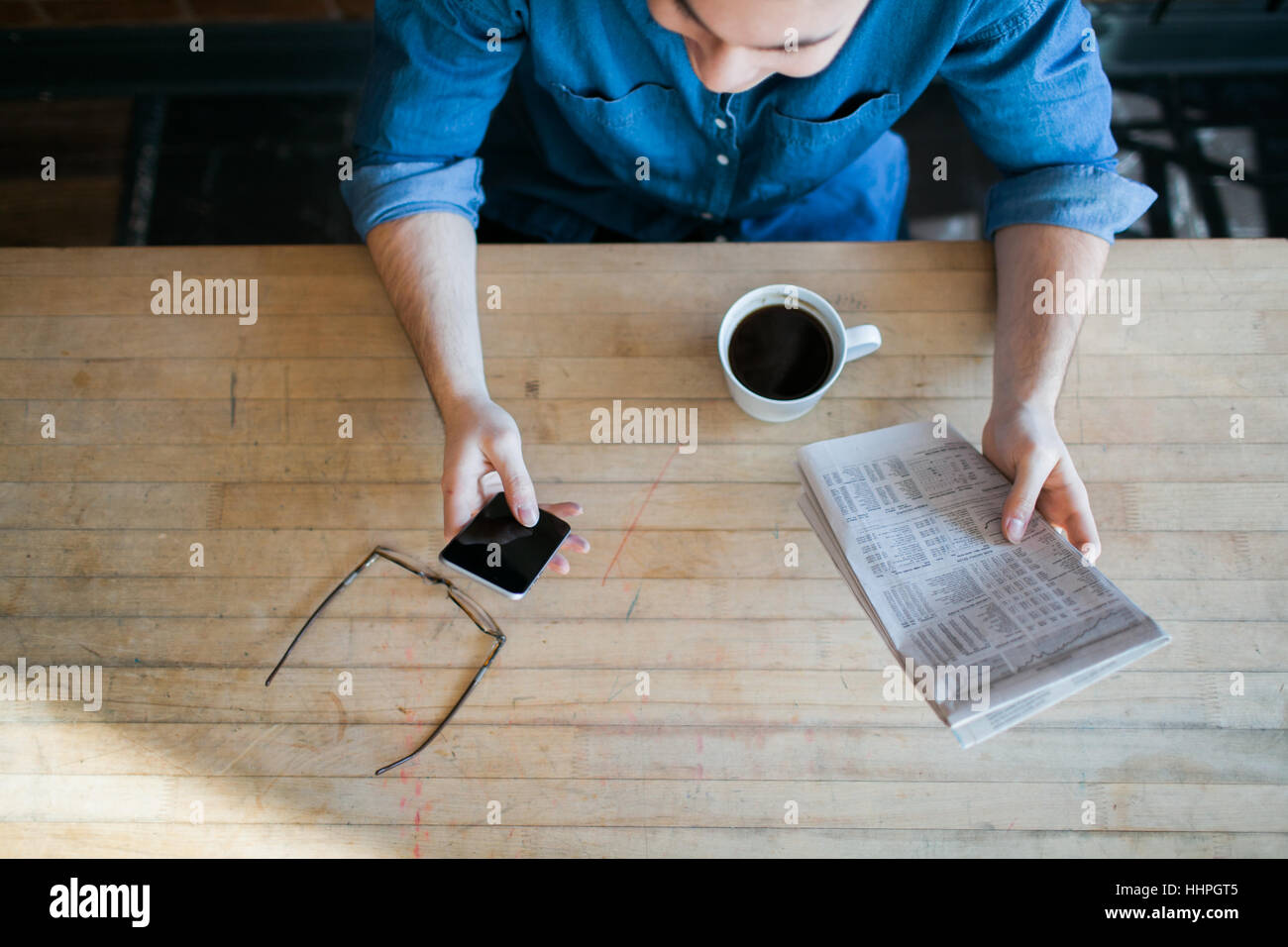 Young man reading paper and phone, drinking coffee, sitting at a wooden table in hipster cafe and looking down, - Stock Image
