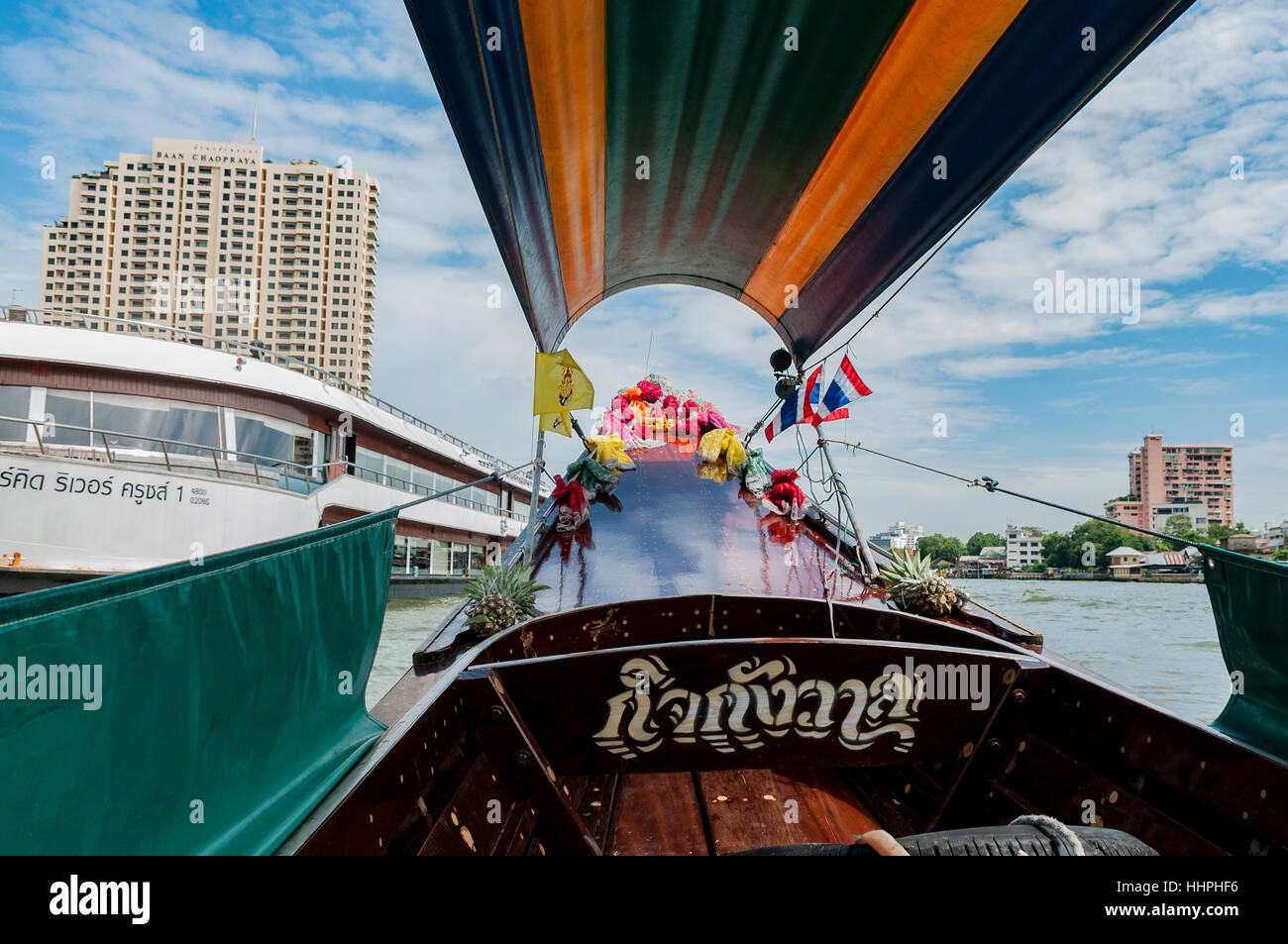 An open-air motorized boat headed down the Chao Phraya River in Bangkok for a tour of the waterways. - Stock Image
