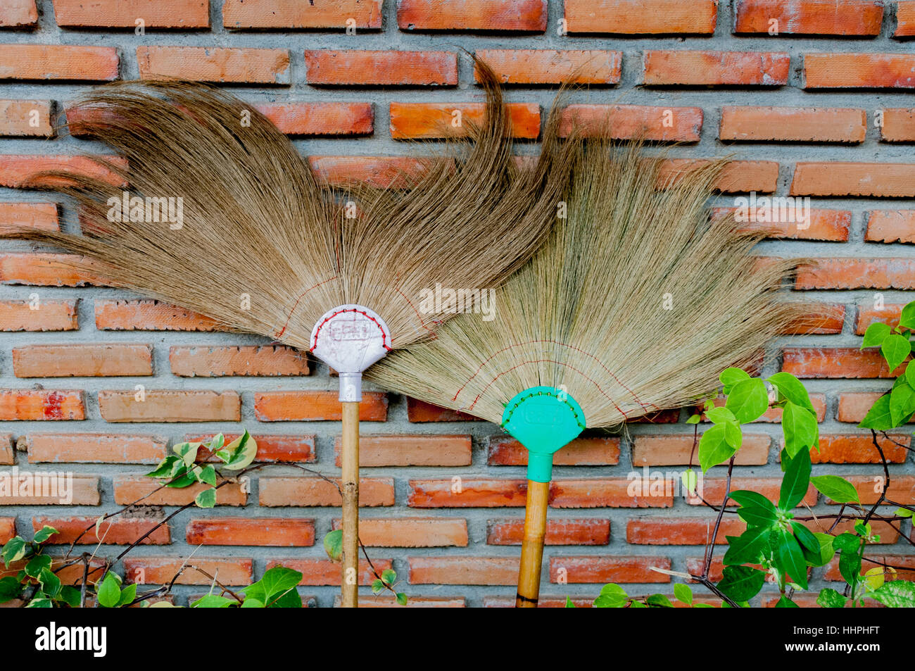 Two traditional Thai brooms against a brick wall, with some green leaves, in Ban Chiang, Northeast Thailand. - Stock Image