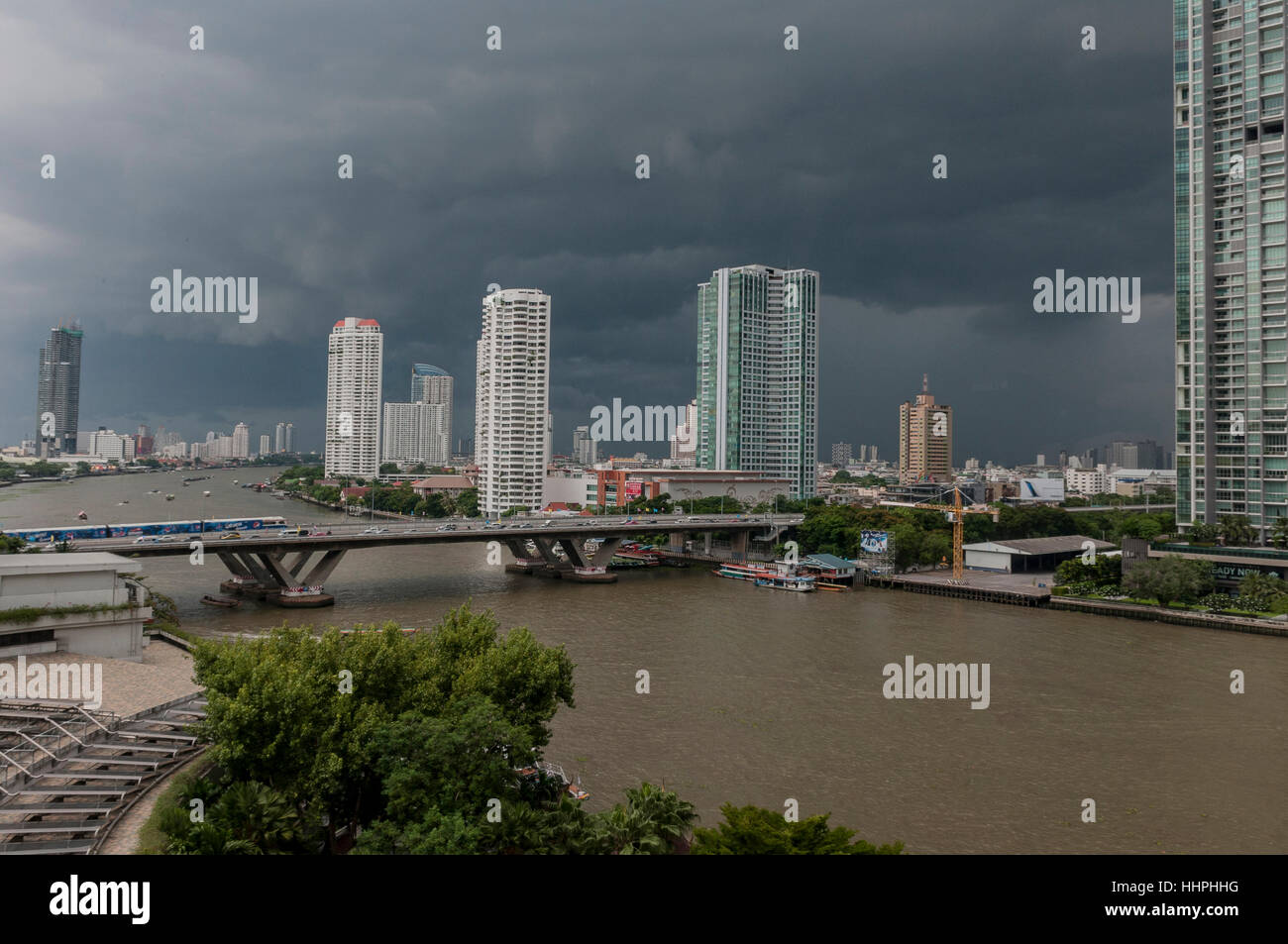 The black sky is a precursor to a heavy rain storm during monsoon season in Bangkok, Thailand. - Stock Image