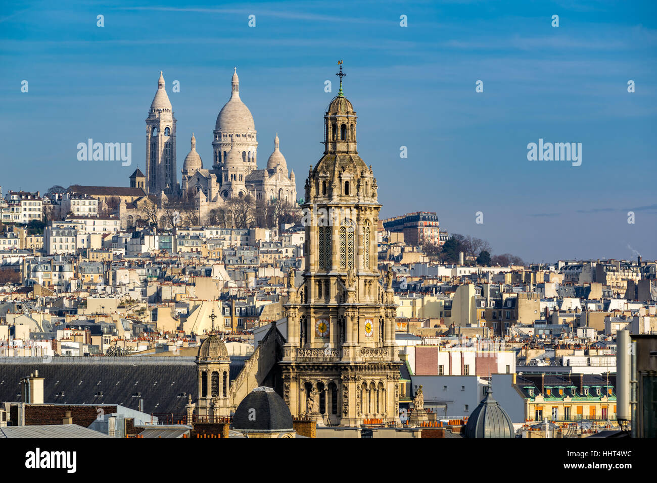Rooftops of Paris with view of the Sacre Coeur Basilica in Montmartre and the Trinity Church. 18th Arrondissement, Stock Photo
