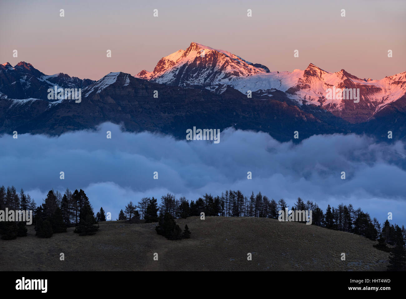 Winter sunset on the Ecrins National Park mountain peaks (Chaillol, Queyrel, Tourond) raising above the clouds. - Stock Image