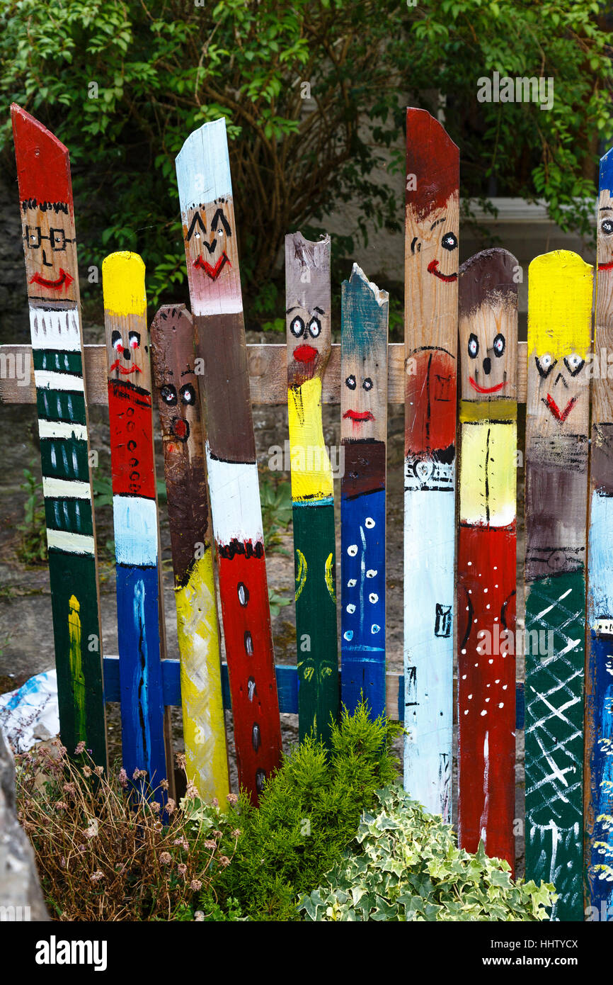 Funny painted faces on a fence in Esch-sur-Sûre, Luxembourg - Stock Image