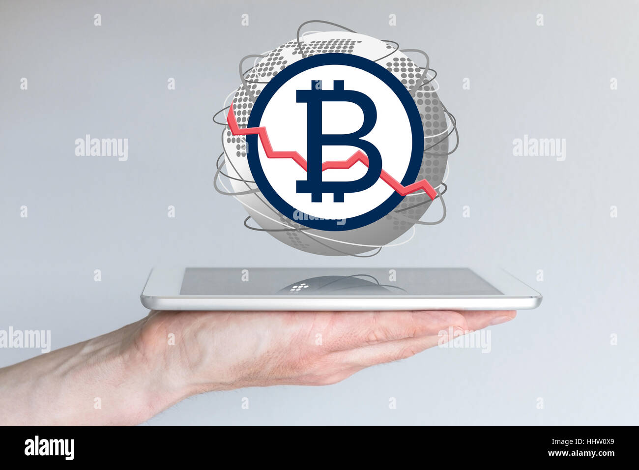 Decline of global bitcoin currency exchange rate concept with hand holding tablet - Stock Image