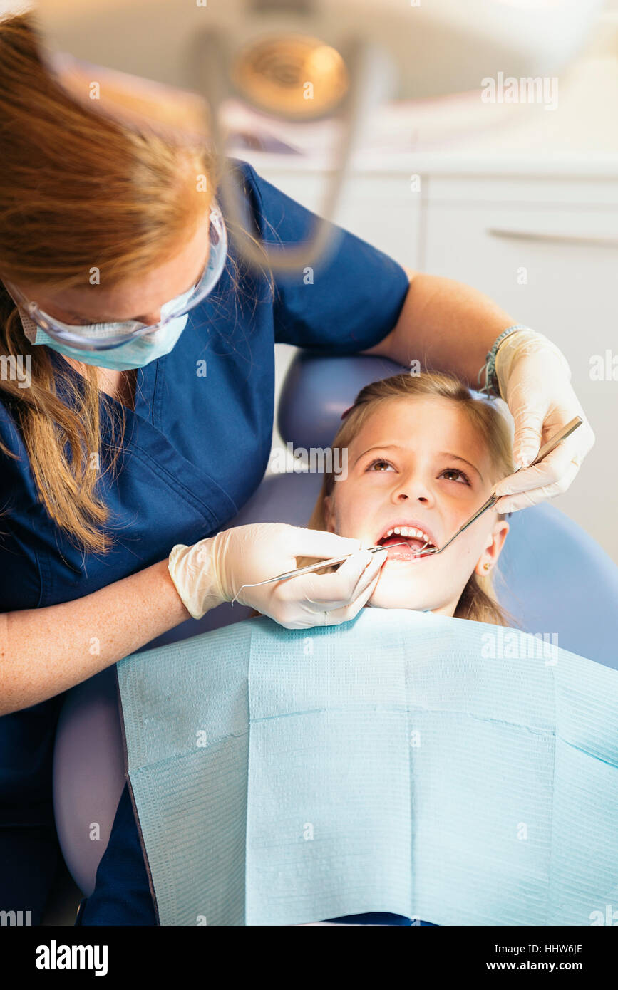 ntists with a patient during a dental intervention to girl. - Stock Image