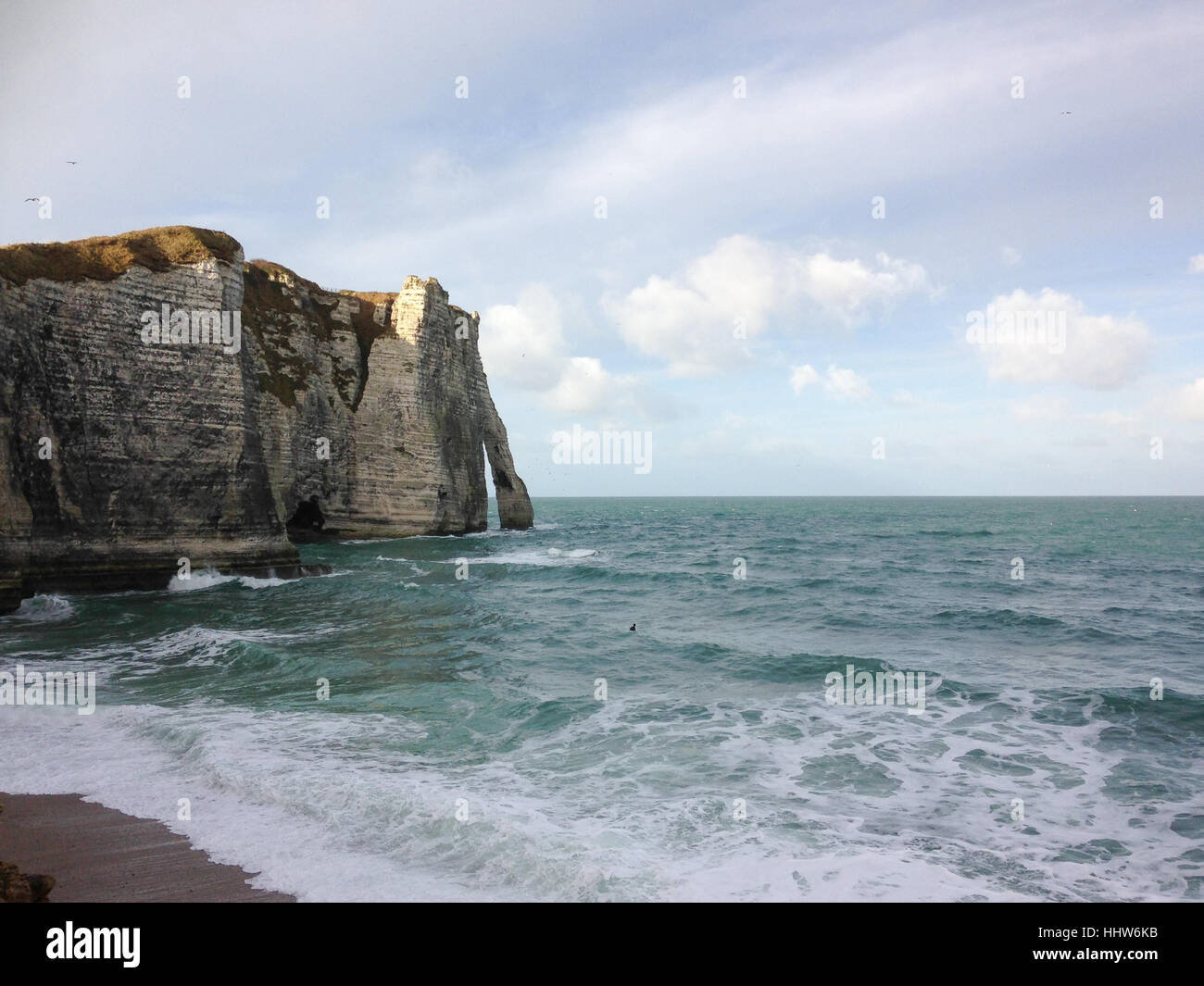 View on Falaise d'Etretat with surfer in the water Stock Photo